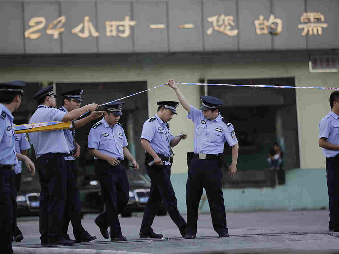 Police officers walk out from the main gate of Weng's Cold Storage Industrial Co. Ltd. at the outskirts of Shanghai, China, on Saturday.