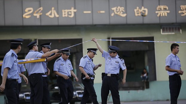 Police officers walk out from the main gate of Weng's Cold Storage Industrial Co. Ltd. at the outskirts of Shanghai, China, on Saturday. (Associated Press)