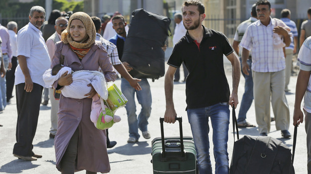 Syrian refugees pass through the Turkish Cilvegozu gate border on Sunday. (Associated Press)