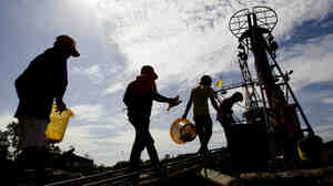 "Migrant workers from Myanmar return to a trawler after unloading fish following a fishing trip in the Gulf of Thailand in Samut Sakhon province Tuesday. A new report details ""deceptive and coercive"" labor practices in the Thai fishing sector, which relies heavily on workers from Cambodia and Myanmar, also known as"