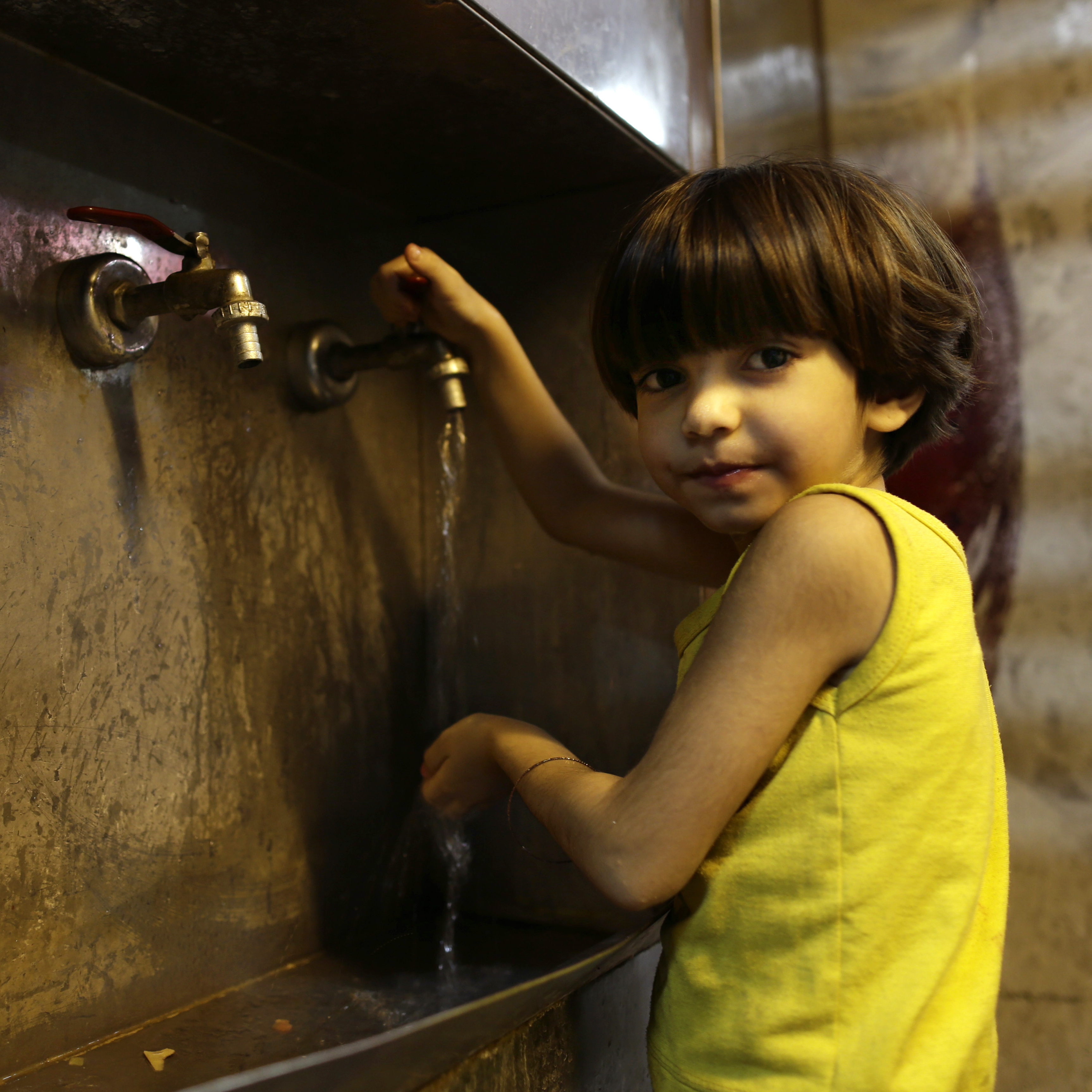 A girl whose family fled their home because of Syria's civil war runs water for drinking in the kitchen of the Kertaj Hotel in Damascus on Aug. 25. Seeking safety, about a dozen families have been living in the hotel for months.