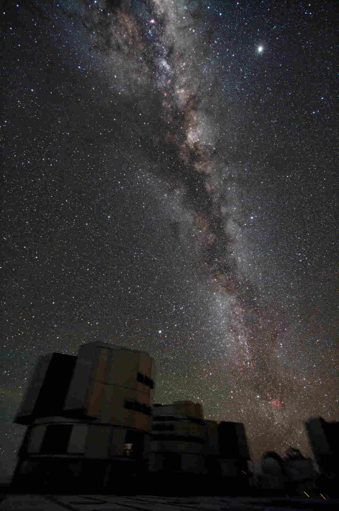The Milky Way fills the night sky over Chile's Cerro Paranal, home to the European Southern Observatory's Very Large Telescope (VLT).
