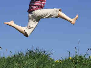 A boy jumps above a grassy field