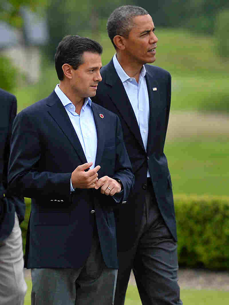 New reports allege that the NSA spied on Mexican President Enrique Pena Nieto, seen here walking with President Barack Obama in June, when he was a candidate for office. Mexico and Brazil have demanded a response to charges of U.S. spying on their internal affairs.