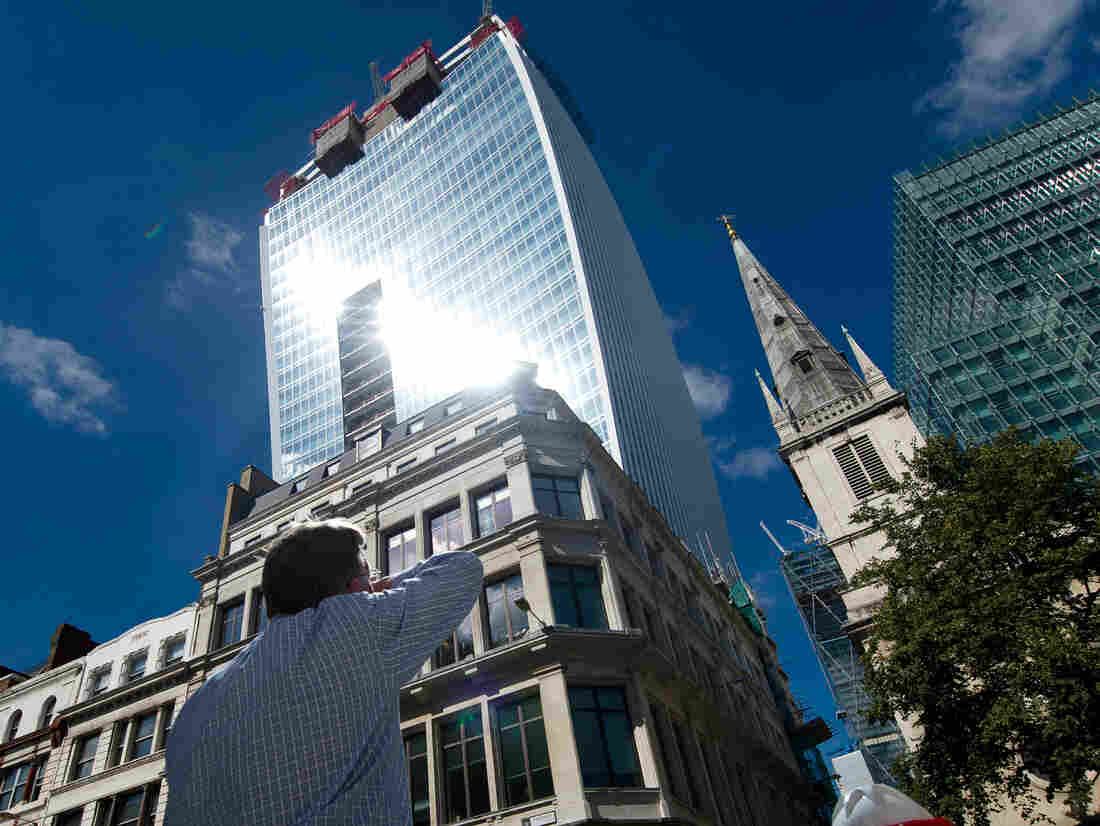"""A man reacts to a shaft of intense sunlight reflected from the glass windows of the new """"Walkie Talkie"""" tower in central London on Aug. 30."""