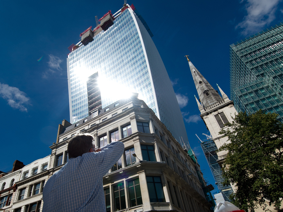"A man reacts to a shaft of intense sunlight reflected from the glass windows of the new ""Walkie Talkie"" tower in central London on Aug. 30. (Leon Neal/AFP/Getty Images)"