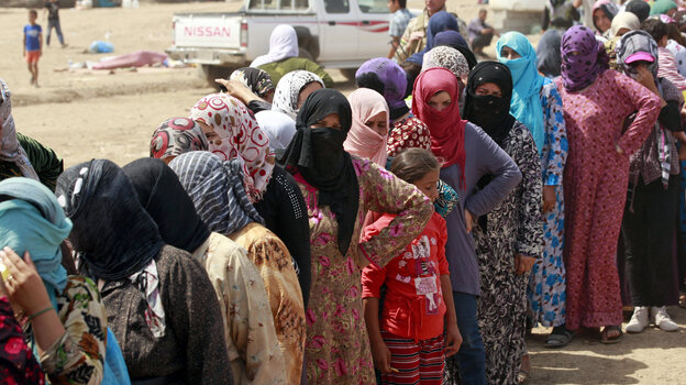 Syrian refugees stand in line for food at Kawergost refugee camp in Irbil, Iraq, on Aug. 21. The Syrian civil war has already sparked a refugee crisis in the region. Now, many countries are waiting to see the effects of a possible U.S. military strike.