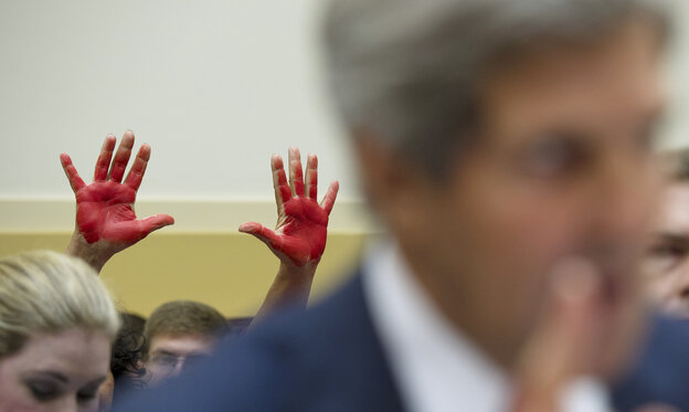 """As Secretary of State John Kerry spoke to the House Foreign Affairs Committee on Wednesday, """"Code Pink"""" protesters behind him held up """"bloody hands"""" to express their opposition to the prospect of U.S. military strikes on Syria."""