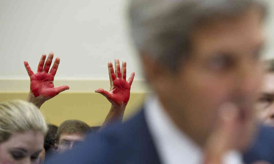 "As Secretary of State John Kerry spoke to the House Foreign Affairs Committee on Wednesday, ""Code Pink"" protesters behind him held up ""bloody hands"" to express their opposition to the prospect of U.S. military strikes on Syria."