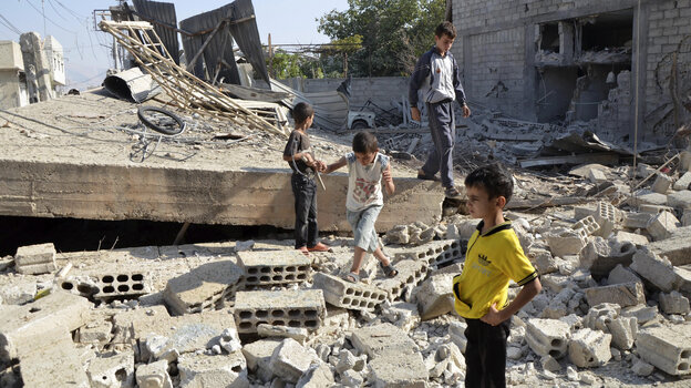 Syrian boys walk on the rubble of a building in Damascus that was hit by what activists said was shelling by government forces. The threat of a possible U.S. strike has added to the sense of unease in the Syrian capital.