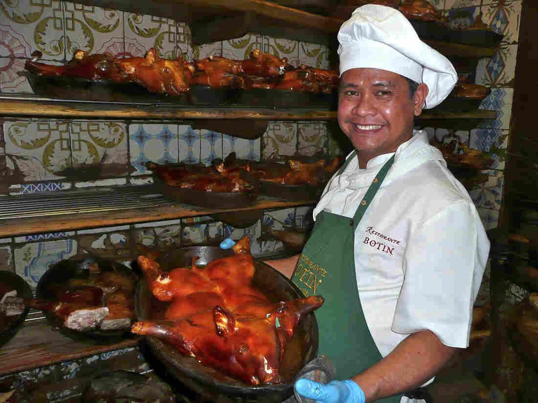 Roel Basalm Alim, a cook at Restaurante Botín, displays a plate of cochinillo asado, or roast suckling pig.