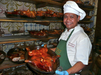 Roel Basalm Alim, a cook at Restaurante Botín, displays a plate of cochinillo asado, or roast suckling pig.