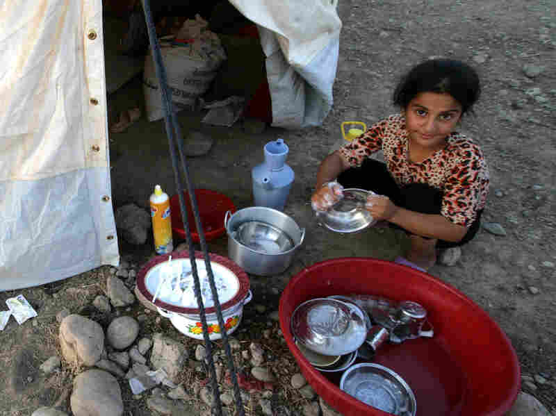 A Syrian girl washes the dishes at the Quru Gusik refugee camp in northern Iraq, last month. More than 2 million Syrians have fled their homeland since the uprising began in 2011.
