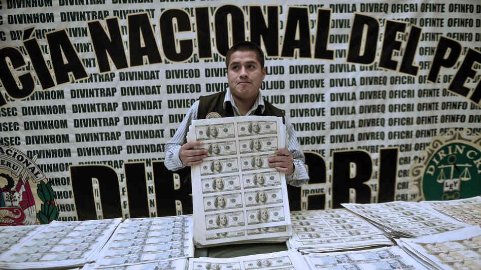 A policeman shows printed sheets of counterfeit bills seized by Peruvian police.