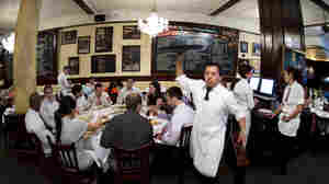 A waiter serves patrons at Tony's Restaurant, part of the Casablanca Hotel in New York's Times Square. The custom at some restaurants of automatic gratuities for larger parties might change because of an IRS rule change.