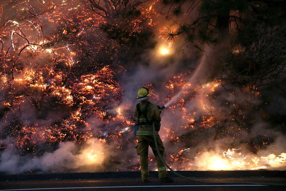 A firefighter uses a hose to douse the flames