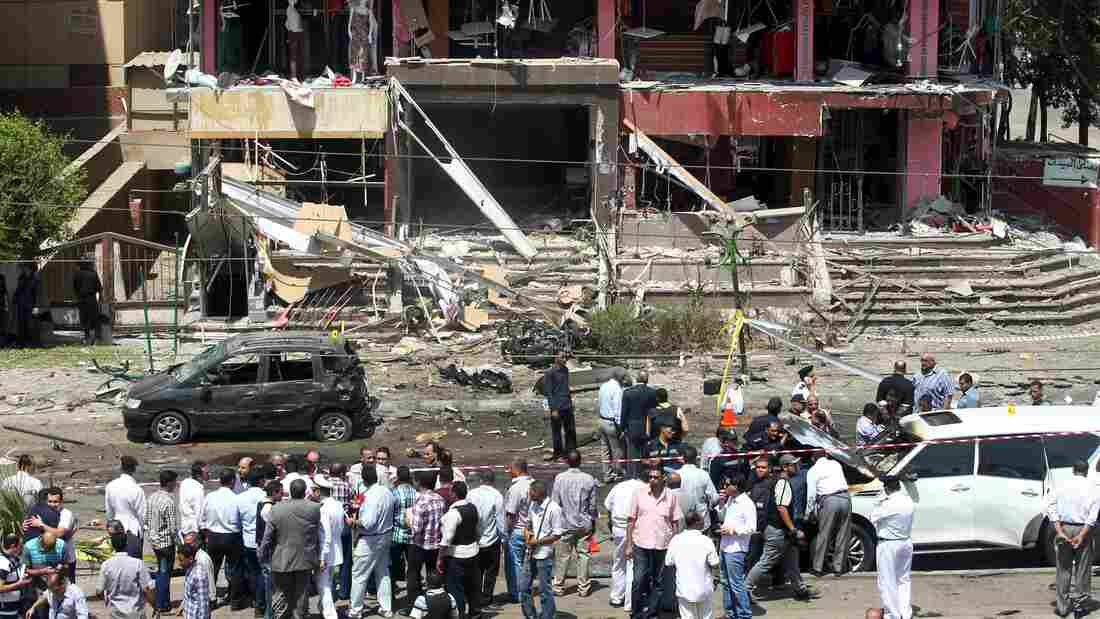 Security officials inspect the scene of a bomb blast that apparently targeted Egyptian Interior Minister Mohammed Ibrahim near his home in Cairo's Nasr City on Thursday. He survived the attack.