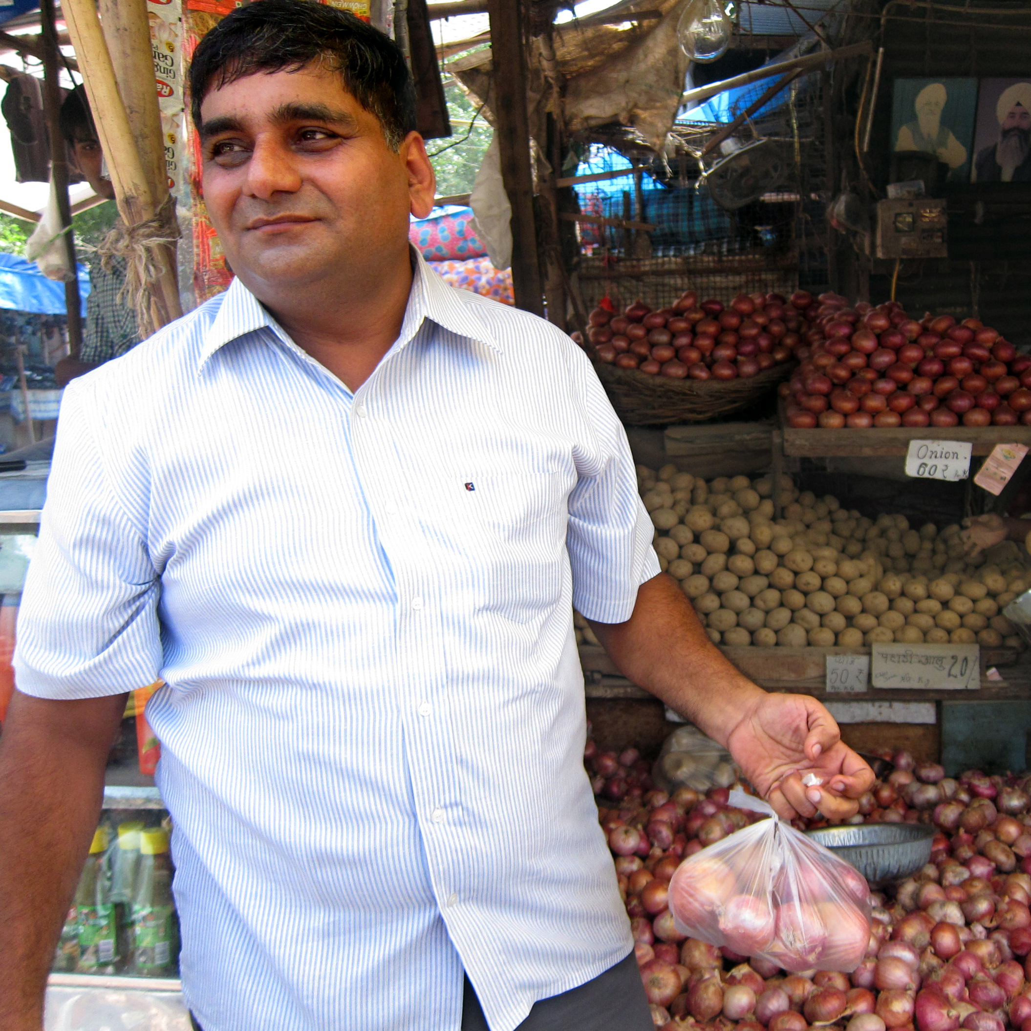 "While shopping at a vegetable stand, wedding videographer Mohammad Saleem said his financial condition now is ""earning and burning."""