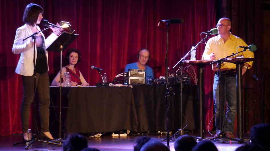 Wait, Wait...Don't Tell Me! host Peter Sagal stands poised and ready for the next perplexing question from Ask Me Another host Ophira Eisenberg, on stage at The Bell House in Brooklyn, NY.