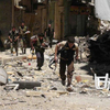Syrian rebel fighters run run for cover during clashes Wednesday with government forces in Aleppo. Syria's largest city has been bitterly divided since heavy fighting broke out more than a year ago. The government army controls the western part of the city; the rebels control the east. Residents risk sniper fire as they cross back and forth.
