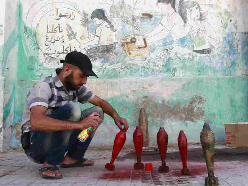 A rebel with the Free Syrian Army spray paints improvised mortar shells at a weapons factory in Aleppo on Thursday.