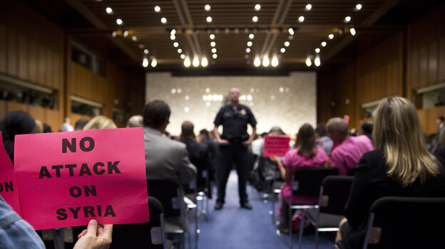A protester holds up a sign against U.S. action in Syria during a Senate Foreign Relations Committee hearing Tuesday. The committee ultimately approved a resolution to give President Obama authorization for a military strike on Syria. The full Senate could vote on the measure this week.