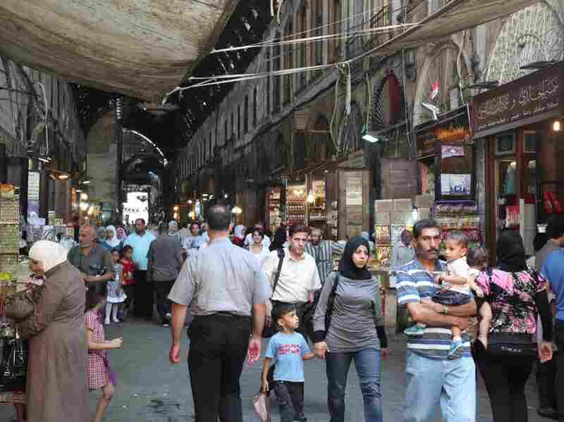 Syrians walk at the al-Bzoureya market in Old Damascus on Thursday.