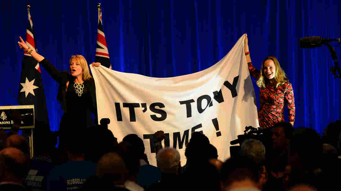 Women hold a banner celebrating Australia's next prime minister, conservative Tony Abbott, in Sydney. Abbott swept away Prime Minister Kevin Rudd, as voters punished Labor for years of internal party warfare.
