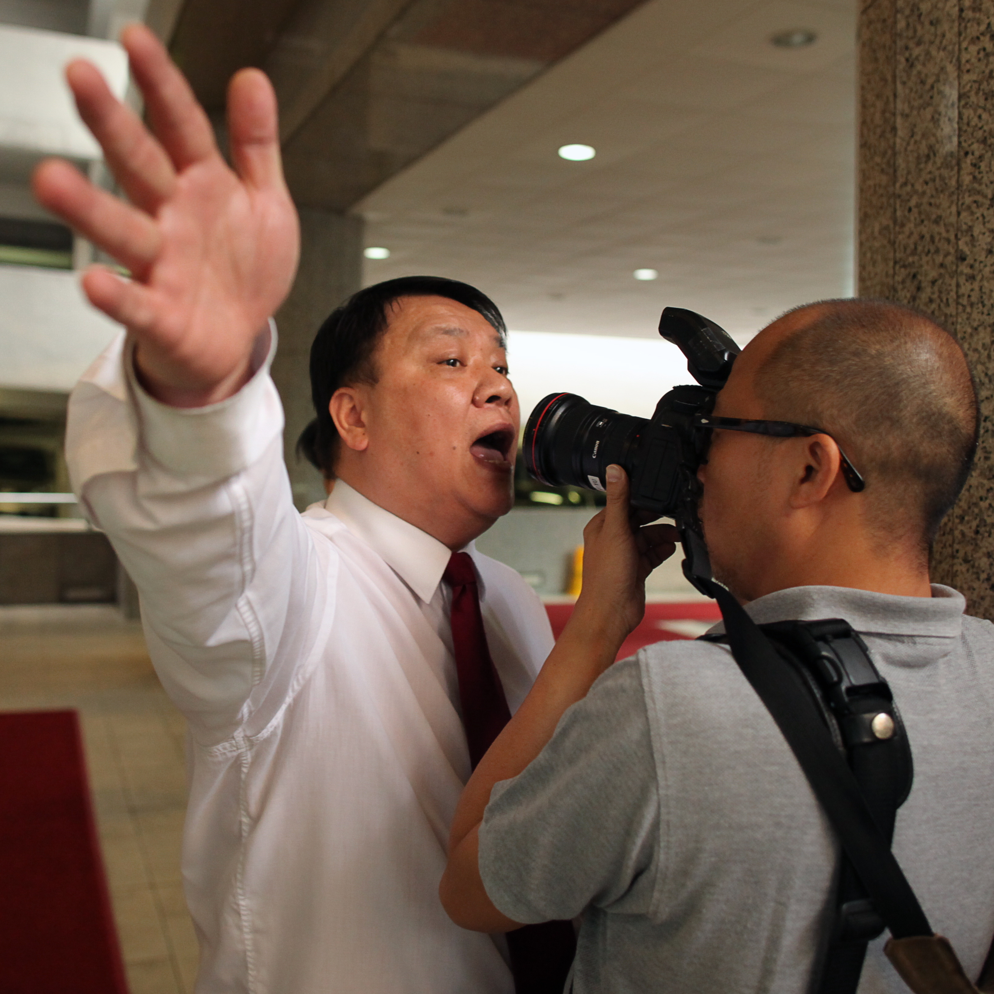 A security guard in Hong Kong makes his own censorship attempt during a protest outside the Thai consulate in 2011.