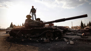 A Free Syrian Army fighter stands on a damaged military tank in Zabadani, near Damascus on Sunday.