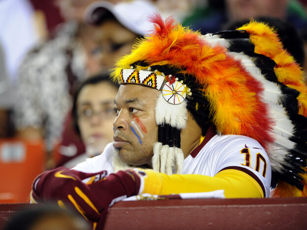 A Washington Redskins fan watches from the sidelines during the first half of an NFL preseason football game this August.