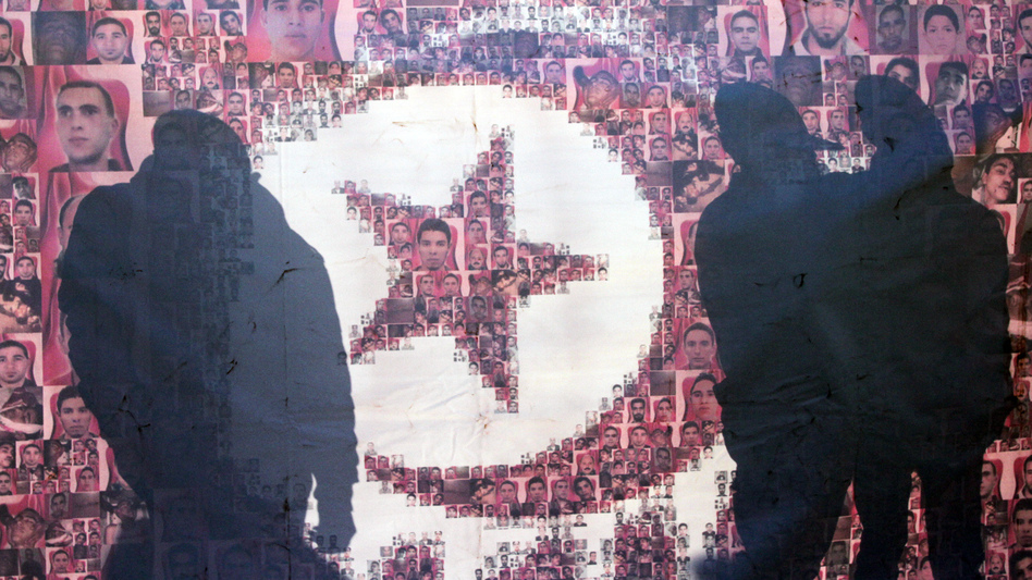 Tunisians are silhouetted Jan. 13 behind a poster of those who died in the revolution that overthrew an authoritarian president and started the Arab Spring. More than two years after the revolution, Tunisia is struggling with high unemployment and rising violence in its politics. (AP)