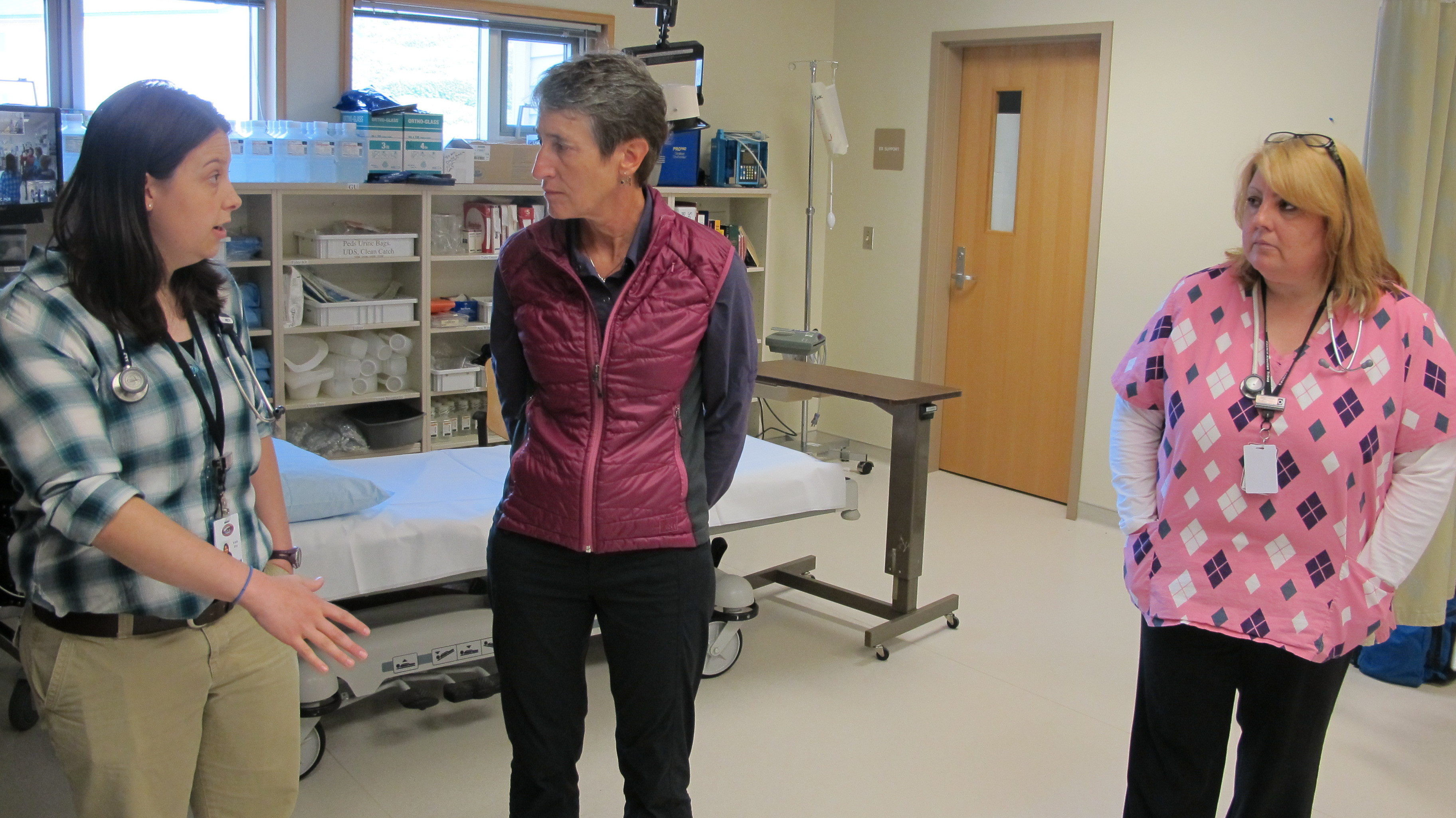 Bonita Babcock (right) looks on as a physician assistant at the clinic in King Cove, Alaska, explains to Interior Secretary Sally Jewell how a road from King Cove to Cold Bay would improve health care.