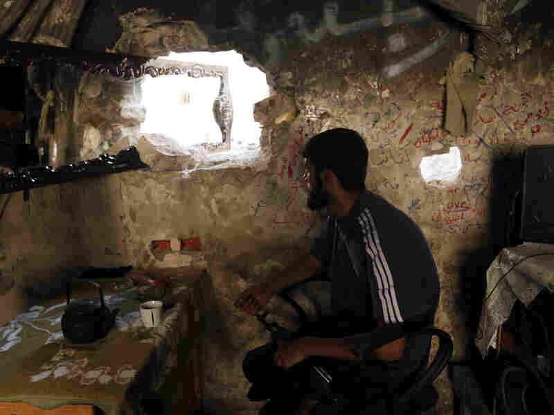 A rebel fighter keeps watch for government troops in Aleppo on Sunday.
