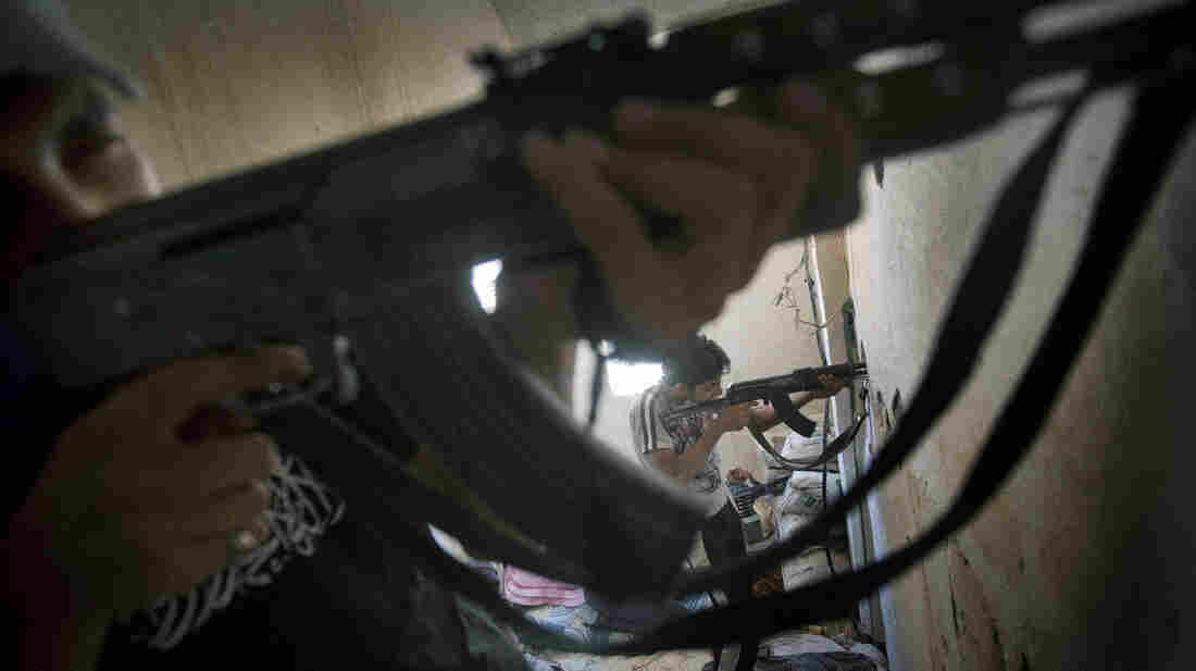 Rebel fighters aim at government troops during fighting in the eastern town of Deir Ezzor on Saturday.