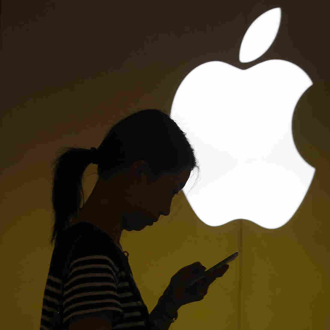 A woman looks at her phone in front of the Apple store in Shanghai. Apple unveiled a cheaper version of the iPhone on Tuesday.