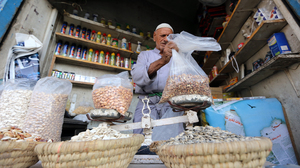 A man weighs goods at a market in Baghdad on Sept. 1. Baghdad's once-bustling markets are facing difficult times as customers stay away, increasingly fearful of bomb attacks.