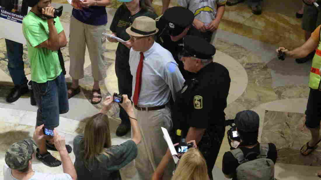 Police arrest a protester for singing without a permit inside the Wisconsin Capitol in Madison, on Aug. 1.