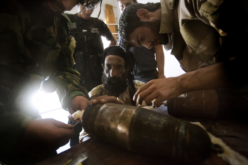 Rebel fighters prepare explosive devices to be used during fighting against Syrian government forces on September 7, 2013 in Syria's eastern town of Deir Ezzor.
