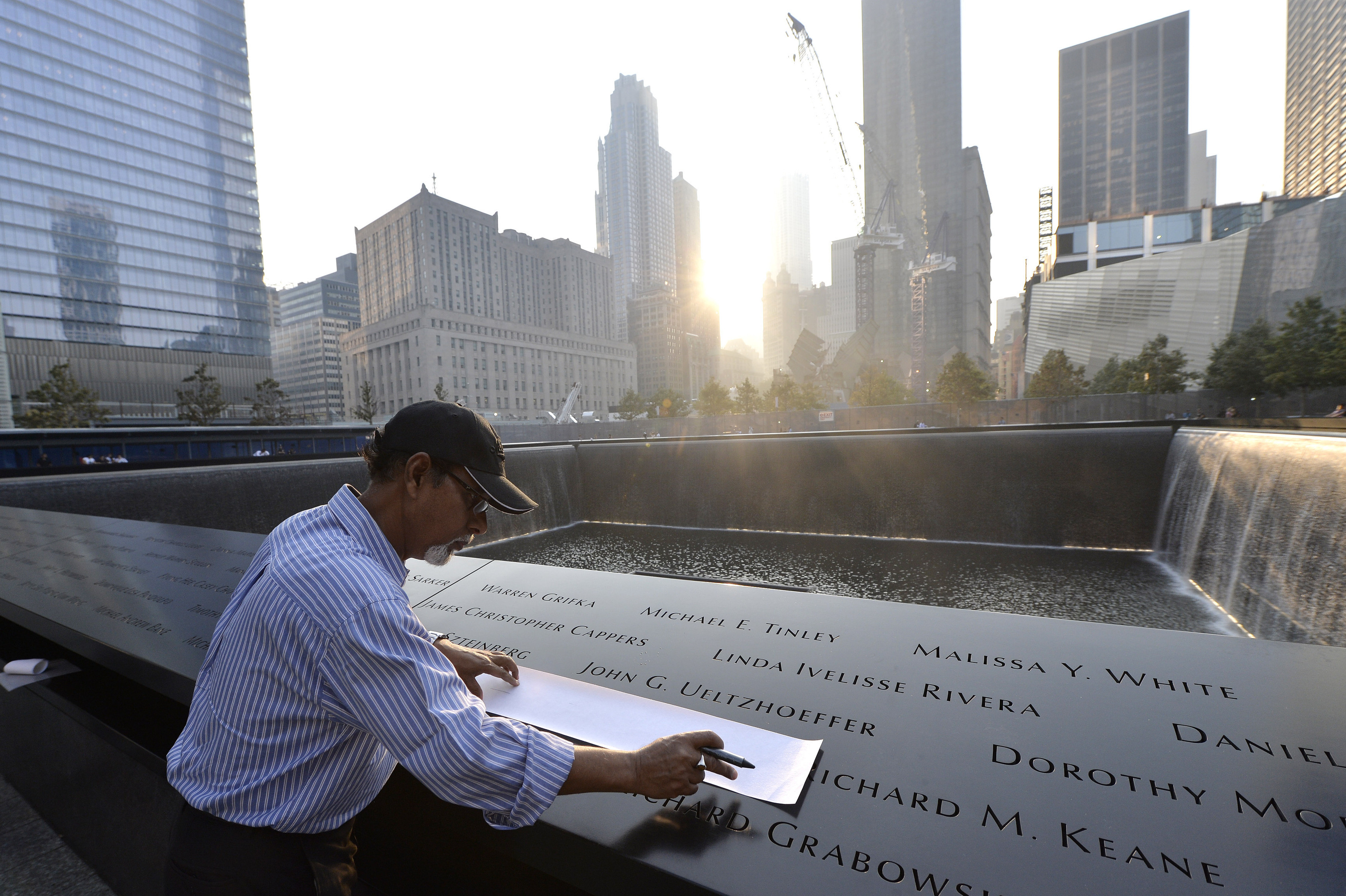 Wakiley Ramen Chowdhury makes a rubbing of his niece's name, Shakila Yasmin, at the edge of the North Pool at the 9/11 Memorial.
