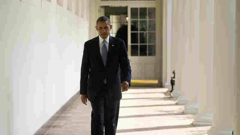 President Obama walks along the West Wing Colonnade toward the