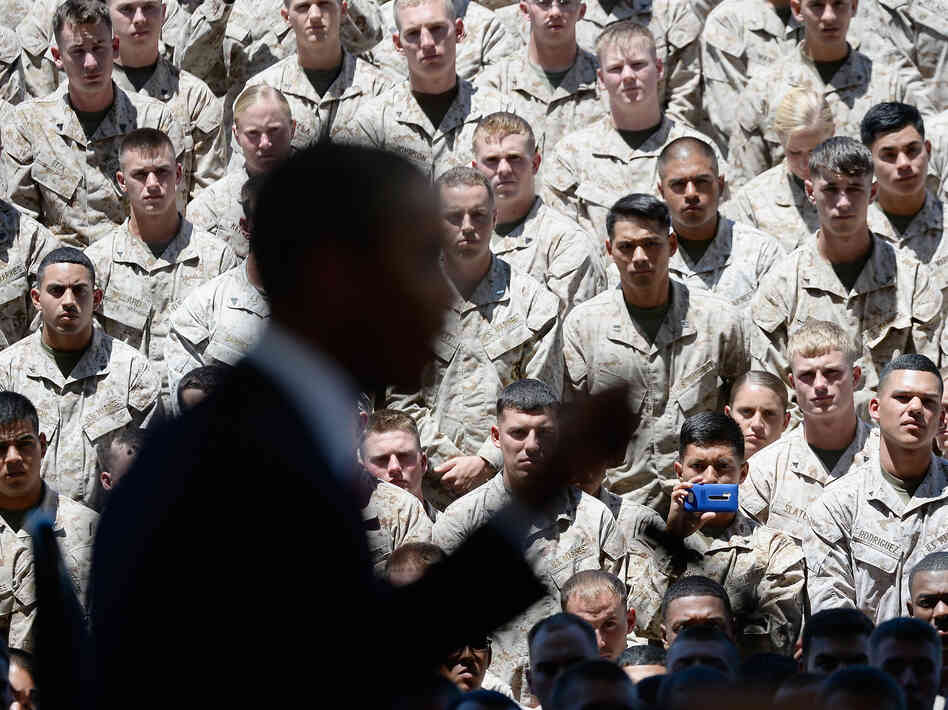 Members of the U.S. Marine Corps listen to President Obama during his visit to Camp P