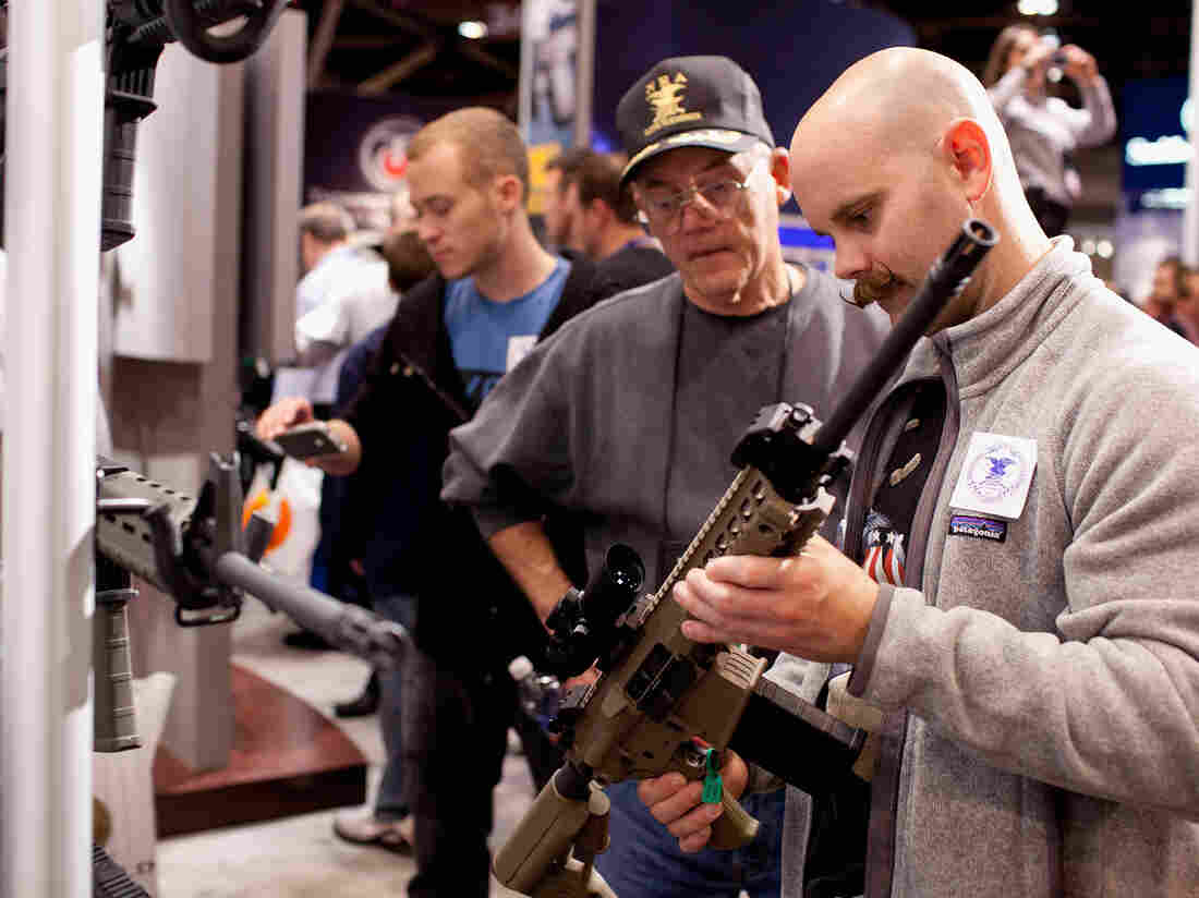 George Sherer and his son, Jeff, look at a SIG Sauer 716 patrol rifle during the NRA Annual Meetings and Exhibits last April in St. Louis.