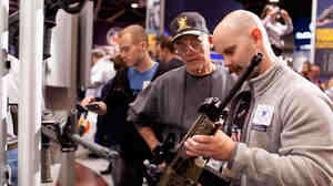 George Sherer and his son, Jeff, look at a SIG Sauer 716 patrol rifle during the NRA