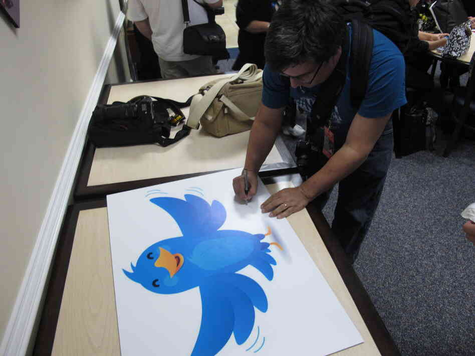 In this Nov. 8, 2011, photo, NASA fan David Parmet signs his name on a Twitter logo during a tweetup event for about 50 of NASA's Twitter followers at the Langley Research Center in Hampton, Va.