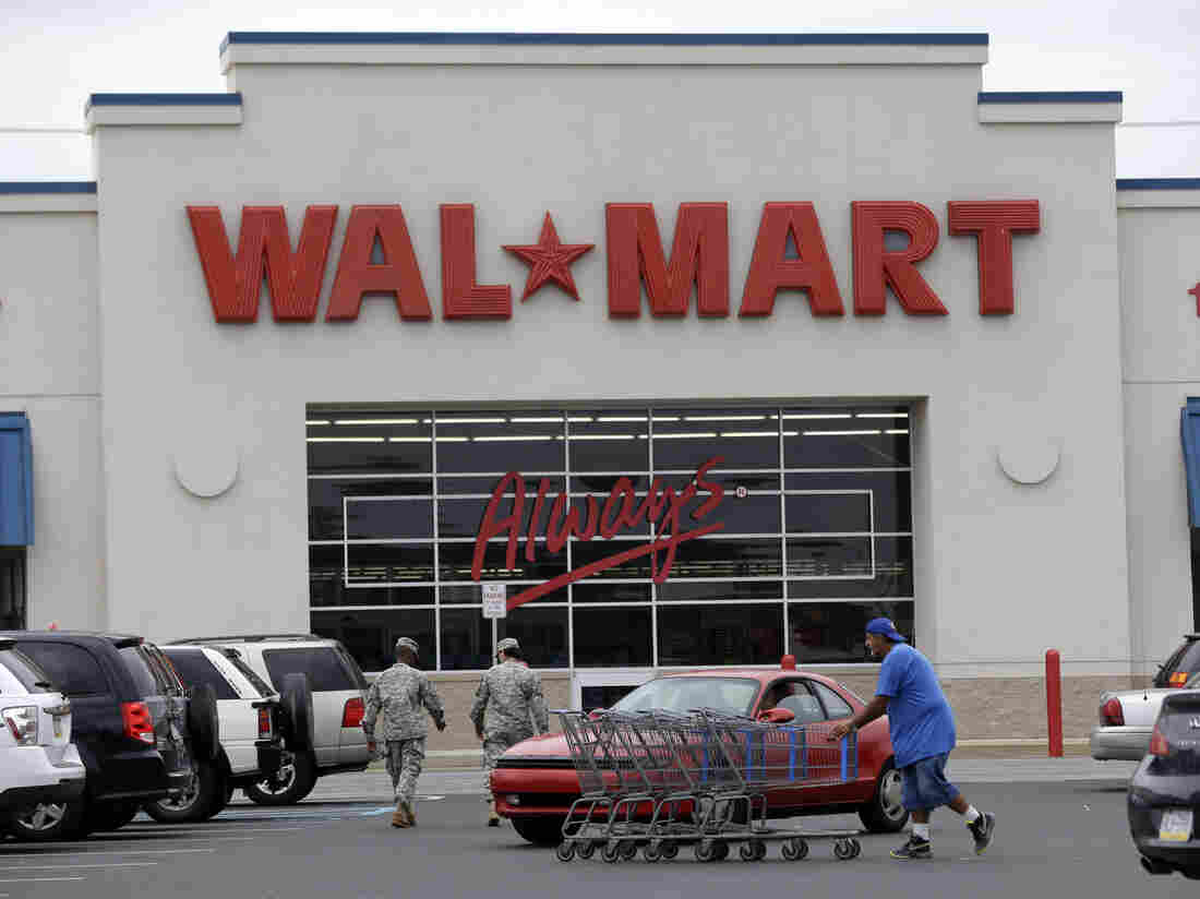 A worker collects shopping carts at a Wal-Mart parking lot, in Bristol, Pa.