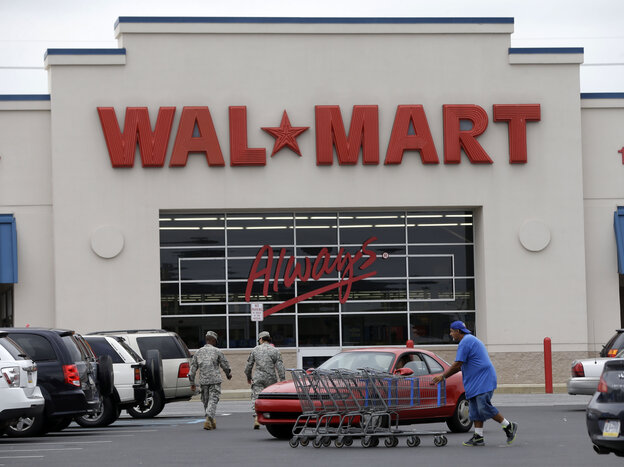 A worker collects shopping carts at a Wal-Mart parking lot, in Bris