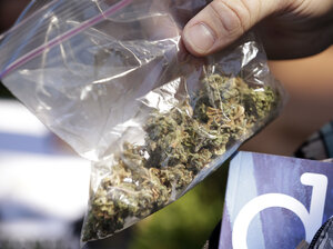 A man pulls out a bag of marijuana to fill a pipe at Hempfest in Seattle on Aug. 16. Thousands packed a waterfront park for the opening of a three-day marijuana festival, an event that is part party, part protest and part victory celebration after the legalization of pot in Washington and Colorado in 2012.