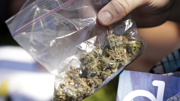 A man pulls out a bag of marijuana to fill a pipe at Hempfest in Seattle on Aug. 16. Thousands packed a waterfront park for the opening of a three-day marijuana festival, an event that is part party, part protest and part victory celebration after the legalization of pot in Washington and Colorado in 2012. (AP)