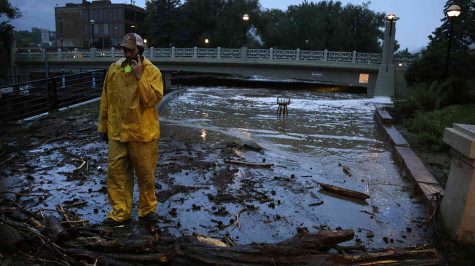 A city worker talks on his phone while surveying high water levels on Boulder Creek following overnight flash flooding in downtown Boulder, Colo. today. Flash flooding in Colorado has left two people dead and the widespread high waters are keeping search and rescue teams from reaching stranded residents and motorists in Boulder and nearby mountain communities.